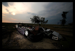23 June, 2006. New Orleans, Louisiana. Upside down car. Lower 9th ward. Sunset. Many months after hurricane Katrina, cars still remain upside down awaiting clearance in the Lower 9th ward.