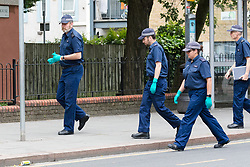 © Licensed to London News Pictures. 27/05/2019. London, UK.  Police search teams at the crime scene in St Paul's Way, Mile End in Tower Hamlets, where a 23 year old man was stabbed multiple times yesterday, 26th May and died overnight in hospital.  Photo credit: Vickie Flores/LNP