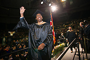 Elliot White waves to supporters at graduate commencement. Photo by Ben Siegel
