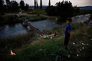 Clearing brush along the banks of the Ibar River in the divided city of Mitrovica, Kosovo.