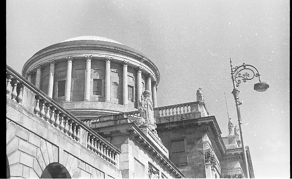 """The Four Courts..1971..16.04.1971..04.16.1971..16th April 1971..The Four Courts,for centuries,has been the centre of Ireland's Judicial system..Work based on the designs of Thomas Cooley, architect of the Royal Exchange (now City Hall), began in 1776. Cooley's building concentrated in the area of the west courtyard and was intended to house only the Public Records Office and King's Inns. When Cooley died in 1784, James Gandon, architect of the Custom House, was appointed to add the courts to the plan. Into his completed design he incorporated Cooley's building, adding two quadrangles and a central block. The quadrangles were given to the record and legal offices, the centre to the four courts of Chancery, Exchequer, Kings Bench and Common Pleas. At the hub is the Round Hall, 64ft in diameter, with inner and outer domes and a surround of Corinthian columns. It was once described as """"both the physical and spiritual centre of the building""""(www.courts.ie/courts.ie/library3.).Throughout the years the courts have been damaged ,destroyed and rebuilt as a result of rebellion and the Irish civil war..Here we see an image of the dome and its columns taken from the roadway at Inns Quay."""