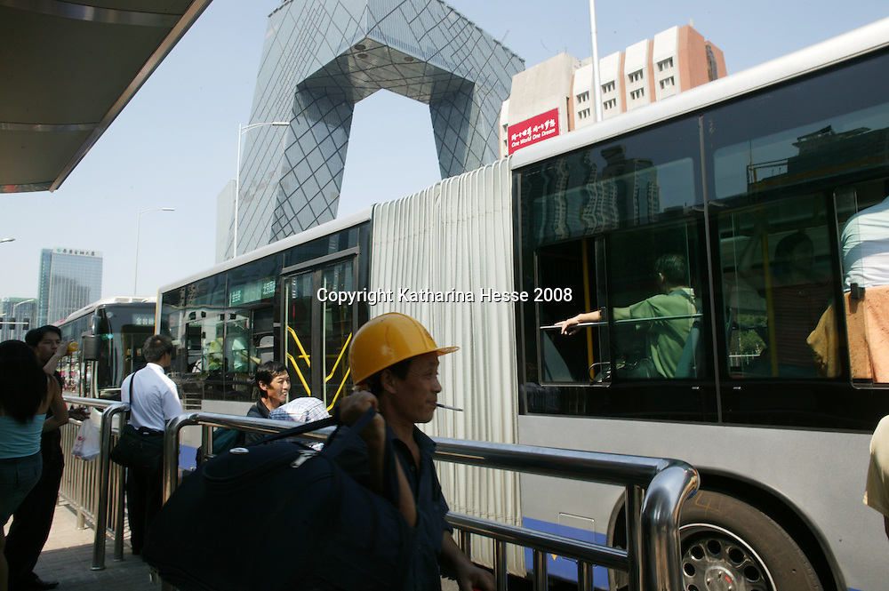 BEIJING, AUGUST-2  : a construction worker stands at a bus-stop near the new CCTV tower.