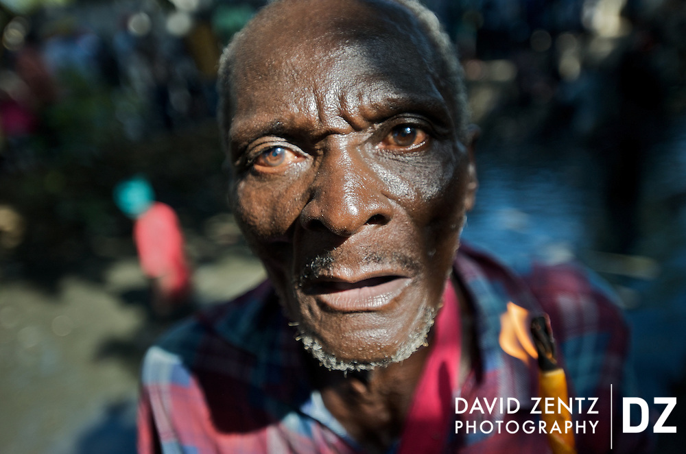 A pilgrim holds a candle to beckon the lwas during the annual Plaine du Nord voodou festival in northern Haiti on July 24, 2008. The baptismal festival centers around St. Jacques' hole, a mud pit on the edge of the village, and honors the lwa Ogou, who presides over matters of war, politics, fire and iron, as well as St. James, the Catholic warrior saint.