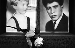 A rose has been placed at the photographs of one of the youngest victims of the Berlin Wall who was killed while trying to escape East Germany. The photographs are part of a memorial at one of the few remains of the Berlin Wall that still exist in Berlin in 2013.
