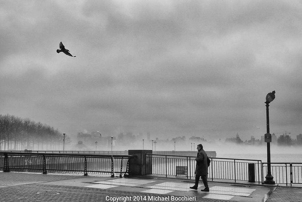 HOBOKEN, NJ - April 08:  A man walks on a foggy morning along the Hudson River on April 08, 2014 in HOBOKEN, NJ.  (Photo by Michael Bocchieri/Bocchieri Archive)