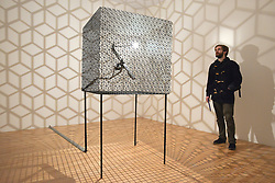 """© Licensed to London News Pictures. 29/01/2013. London, UK A man looks at Conrad Shawcross' """"Slow Arc inside a Cube iV (2009). Press preview of """"Light Show"""" at the Hayward Gallery at the Southbank Centre in London today 29th January 2013. The exhibition runs 30th Jan-28th Apr 2013. Photo credit : Stephen Simpson/LNP"""