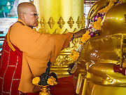 """09 SEPTEMBER 2013 - BANGKOK, THAILAND: A Buddhist monks blesses a statue of the Buddha during Ganesha Chaturthi celelbrations at Shiva Temple. Ganesha Chaturthi also known as Vinayaka Chaturthi, is the Hindu festival celebrated on the day of the re-birth of Lord Ganesha, the son of Shiva and Parvati. The festival, also known as Ganeshotsav (""""Festival of Ganesha"""") is observed in the Hindu calendar month of Bhaadrapada. The date usually falls between 19 August and 20 September. The festival lasts for 10 days, ending on Anant Chaturdashi. Ganesha is a widely worshipped Hindu deity and is revered by many Thai Buddhists. Ganesha is widely revered as the remover of obstacles, the patron of arts and sciences and the deva of intellect and wisdom.     PHOTO BY JACK KURTZ"""