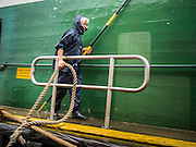 13 AUGUST 2013 - HONG KONG: A Star Ferry worker pulls a rope from a Star Ferry ship to shore during Typhoon Utor in Hong Kong. Typhoon Utor (known in the Philippines as Typhoon Labuyo) is an active tropical cyclone located over the South China Sea. The eleventh named storm and second typhoon of the 2013 typhoon season, Utor formed from a tropical depression on August 8. The depression was upgraded to Tropical Storm Utor the following day, and to typhoon intensity just a few hours afterwards. The Philippines, which bore the brunt of the storm, reported 1 dead in a mudslide and 23 fishermen missing at sea. The storm brushed by Hong Kong bringing several millimeters of rain and moderate winds to the island but causing no reported damage or injuries. It is expected to make landfall in China.   PHOTO BY JACK KURTZ