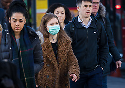© Licensed to London News Pictures. 16/03/2020. London, UK. A commuter wearing a face mask walks across London Bridge this morning. New cases and fatalities resulting from the COVID-19 strain of the Coronavirus continue to be reported daily in the UK with major sporting fixtures cancelled and people advised to stay at home if they have a cough and high temperature. Photo credit: Vickie Flores/LNP