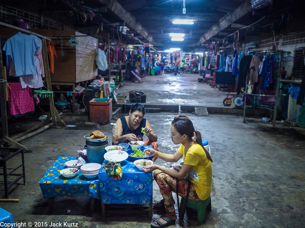 """11 JUNE 2015 - MAHACHAI, SAMUT SAKHON, THAILAND:   Burmese migrant workers eat their lunch in the bottom floor of a tenement building used for migrant housing in Mahachai. Labor activists say there are about 200,000 migrant workers from Myanmar (Burma) employed in the fishing and seafood industry in Mahachai, a fishing port about an hour southwest of Bangkok. Since 2014, Thailand has been a Tier 3 country on the US Department of State Trafficking in Persons Report (TIPS). Tier 3 is the worst ranking, being a Tier 3 country on the list can lead to sanctions. Tier 3 countries are """"Countries whose governments do not fully comply with the minimum standards and are not making significant efforts to do so."""" After being placed on the Tier 3 list, the Thai government cracked down on human trafficking and has taken steps to improve its ranking on the list. The 2015 TIPS report should be released in about two weeks. Thailand is hoping that its efforts will get it removed from Tier 3 status and promoted to Tier 2 status.      PHOTO BY JACK KURTZ"""