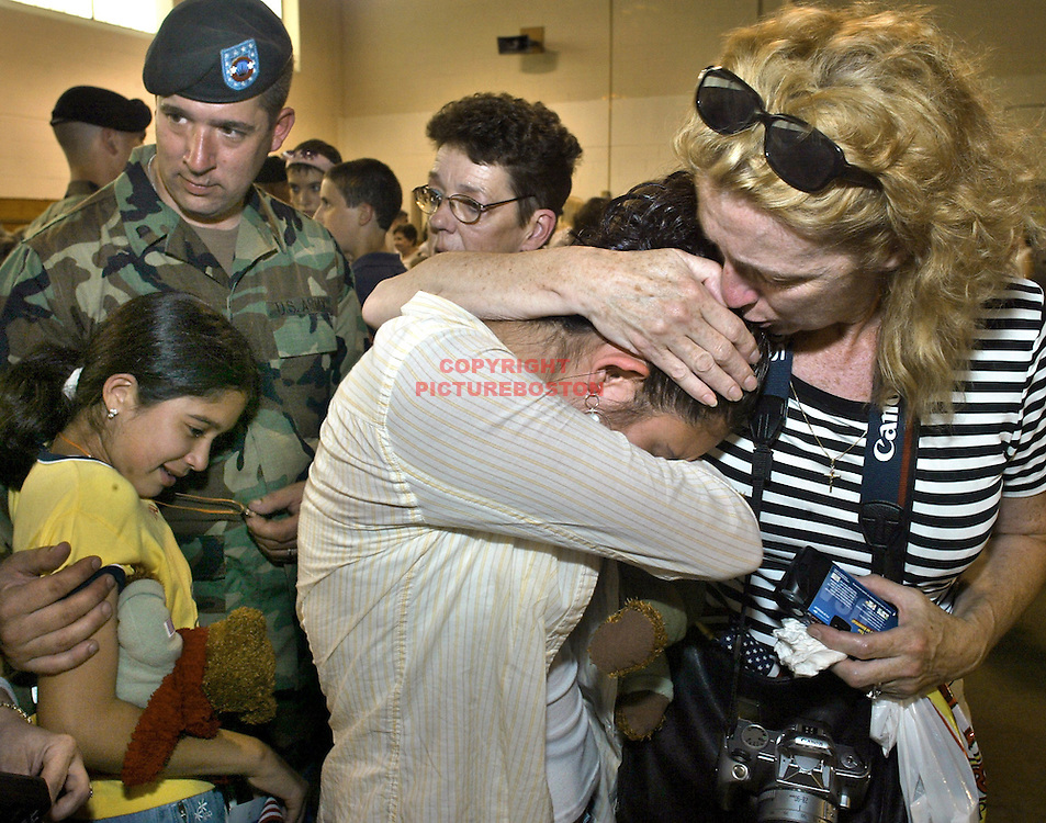 (06/17/04-Reading,MA) Deployment Ceremony for the 272 Chemical Company at Camp Curtis guild. The family of Thomas Lanzoni (who is at far left with daughter Ayaka Lanzoni) reacts to his departure to Iraq....Here, another of Lanzoni's daughters Koto Lanzoni is comforted by her Aunt Seni Cercone.(061704deployedmg-Staff Photo: Mark Garfinkel.Saved photo6/fri)