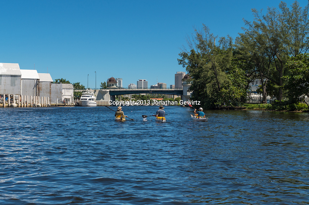 Three kayakers paddle towards downtown Miami on a beautiful day on the Miami River. WATERMARKS WILL NOT APPEAR ON PRINTS OR LICENSED IMAGES.