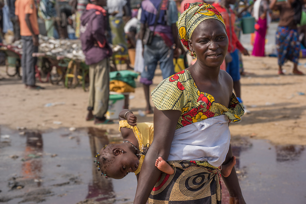 A woman walking with her baby on her back at the Tanju fish market, The Gambia.