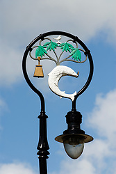 Detail of ornate lamp post showing historic symbols of Glasgow, the salmon with ring and a bell at the Cathedral in Glasgow