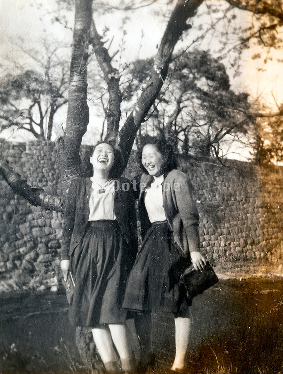 two extreme happy young adult Japanese girls having a good time together ca 1950s