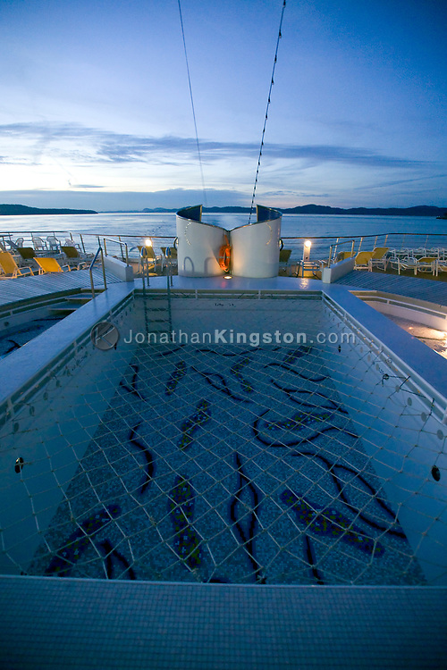 Empty swimming pool onboard the deck of the MV Explorer in the north Pacific.  The MV Explorer is a cruise ship that has been converted into a floating university.