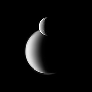 Craters appear well defined on icy Rhea in front of the hazy orb of the much larger moon Titan in this Cassini spacecraft view of these two Saturn moons.