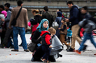 ATHENS, GREECE - FEBRUARY 04: A mother holds his young son while walking toward the buses that will take them to the Macedonian border after disembarking a ferry at the Pireaus port from the Greek islands on February 04, 2015 in Athens, Greece. Thousands of refugees arrive every day by ferries fleet by private companies from the Greek islands to the Pireaus port. Photo: © Omar Havana. All Rights Are Reserved