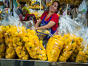 "19 DECEMBER 2013 - BANGKOK, THAILAND:   A marigold vendor in the flower market. Pak Khlong Talat (""the market at the mouth of the canal"") is a market in Bangkok that sells flowers, fruits, and vegetables. It is the primary flower market in Bangkok. It is located on Chak Phet Road and adjacent side-streets, close to Memorial Bridge. The market is open 24 hours, but is busiest before dawn, when boats and trucks arrive with flowers from nearby provinces.       PHOTO BY JACK KURTZ"