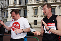 © Licensed to London News Pictures.  14/03/2012. LONDON, UK.  George Eustice, MP for Camborne Redruth and Hayle (pictured left), recovers after winning crosses the line to win the Westminster Mile  in a time of 5 minutes 28 seconds. The Sport Relief Westminster Mile is run by MPs and Peers in St James Park each year in aid of the charity. Photo credit :  Cliff Hide/LNP