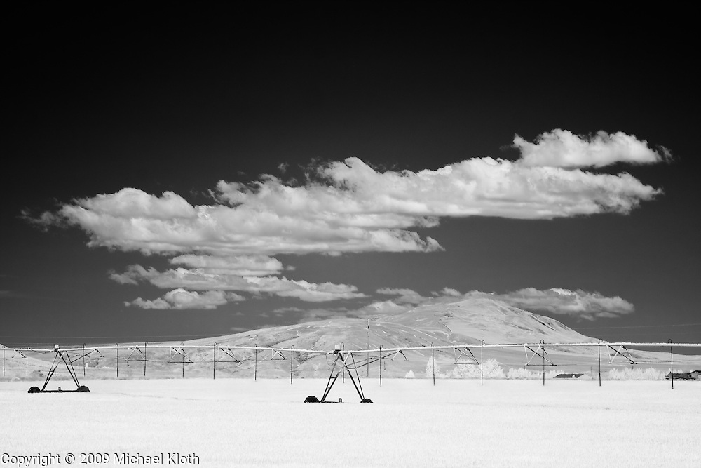 Infrared (IR) photograph of clouds circling Red Mountain near Benton City, Washington.  Red Mountain is photographed beyond a field with irrigation equipment using a camera modified to be sensitive to the infrared spectrum of light.  Photograph by fine art landscape photographer Michael Kloth. Black and white infrared photographs