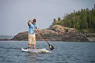 A male stand up paddler paddles hard while excercising on Lake Superior near Marquette Michigan.