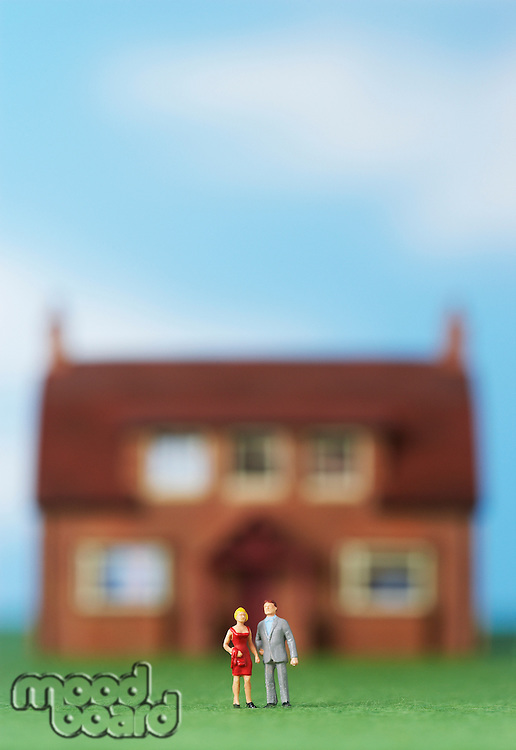 Model people in front of model house