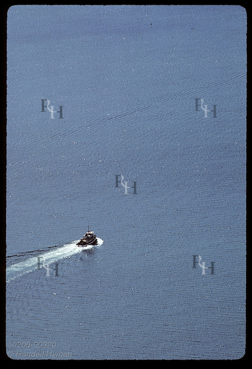 Aerial view of lone boat slicing through the blue-gray waters of Chiniak Bay in August; Kodiak Alaska