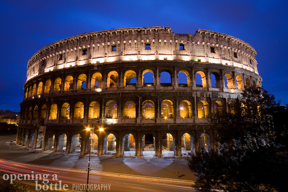Full view of the Roman Coliseum at night with a dark blue sky and Via dei Fori Imperiali below, Rome, Lazio, Italy.