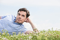 Thoughtful man lying on grass against sky