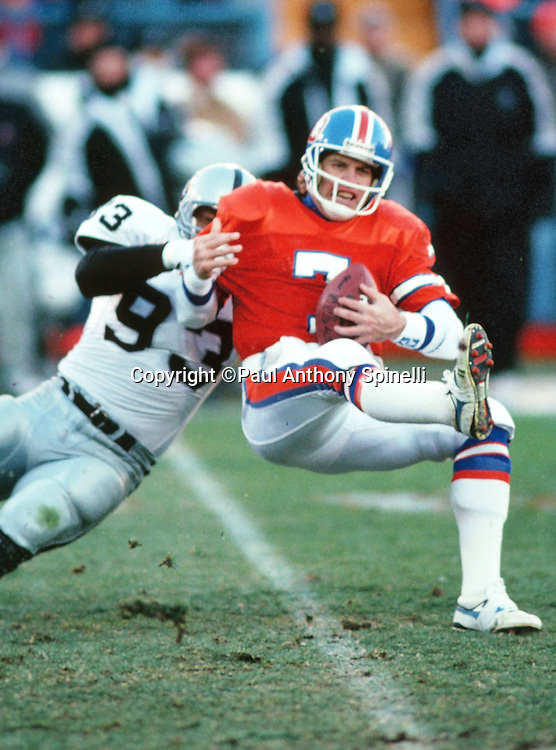 Denver Broncos quarterback John Elway (7) gets sacked by Los Angeles Raiders defensive end Greg Townsend (93) during the NFL football game against the Los Angeles Raiders on Dec. 2, 1990 in Denver. The Raiders won the game 23-20. (©Paul Anthony Spinelli)