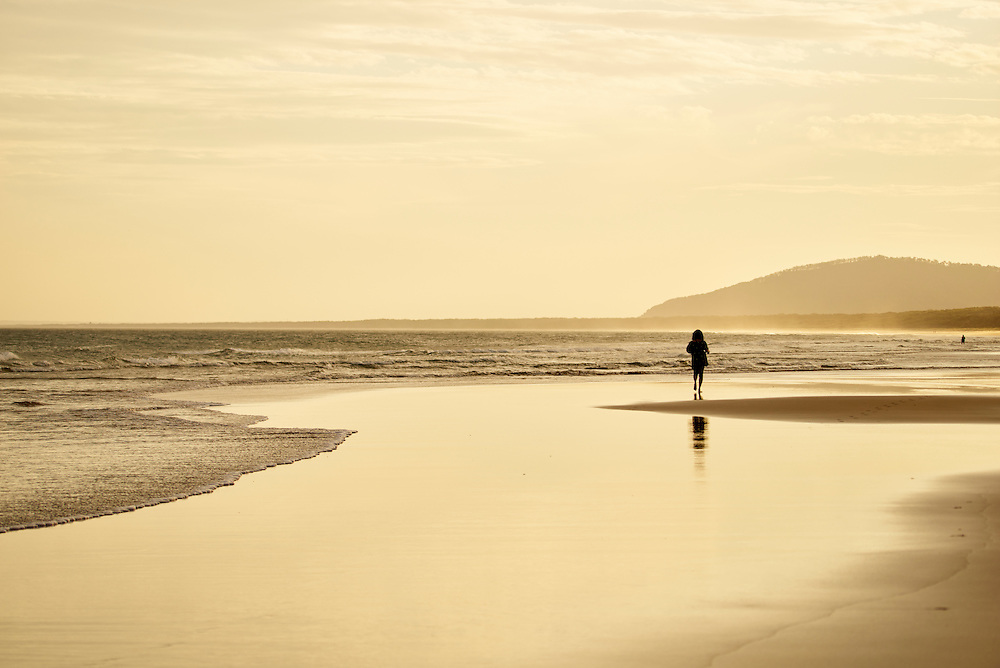 Woman walking on 7 Mile Beach, Gerroa, South Coast, NSW, Australia at sunset.