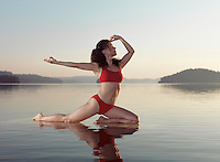 Young woman practicing Hatha yoga on a floating platform in water on the lake during misty sunrise in the morning. Yoga Pigeon posture variation, Kapotasana. Muskoka, Ontario, Canada.