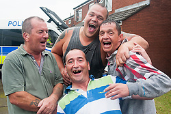Locals pose for a picture during and EDL Rally and UAF Counter demonstration in Doncaster South Yorkshire on Saturday. The EDL and UAF are thought to have chosen Hexthorpe after recent media reports of tension between newly arrived Roma residents and the the local community<br /> <br /> 19 July 2014<br /> Image © Paul David Drabble <br /> www.pauldaviddrabble.co.uk
