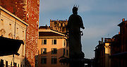 """Low angle view of the Madonna Verona Roman sculpture, 4th century, Piazza delle Erbe, Verona, Italy, silhouetted against the sky. The Piazza delle Erbe (Square of Herbs) stands on the old Roman Forum, and remains the centre of city life. In the centre of the square is a fountain built in 1368, perhaps by Bonino da Campione with a 4th century Roman statue, known as the """"Madonna Verona"""". Picture by Manuel Cohen."""