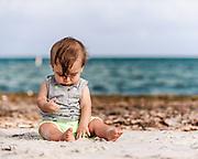 Lucas, surfside, exploring beach sand.