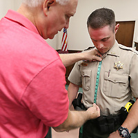Terry Dahlem, with Mid South Uniform out of Jackson, measures Cody Holloway, a sheriff's deputy with Monroe County, for new body armor at the Lee County Justice Center on Friday morning.