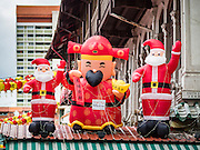27 DECEMBER 2016 - SINGAPORE:   Inflatable Santa Claus figures and a traditional Chinese figure for sale in Chinatown in Singapore.     PHOTO BY JACK KURTZ