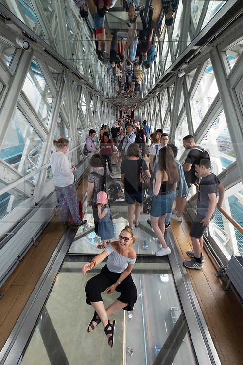 © Licensed to London News Pictures. 30/06/2019. London, UK. Visitors view the glass window inside Tower Bridge. The London landmark celebrate its 125th anniversary today and was open on 30 June 1894. Photo credit: Ray Tang/LNP