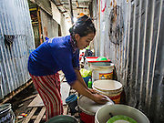 05 SEPTEMBER 2013 - BANGKOK, THAILAND:  A Cambodian woman washes her dishes in the makeshift hallway between corrugated metal dormitories that serve as worker housing at the construction site of a new high rise apartment / condominium building on Soi 22 Sukhumvit Rd in Bangkok. The workers live in the corrugated metal dorms on the site. Most of the workers at the site are Cambodian immigrants.             PHOTO BY JACK KURTZ