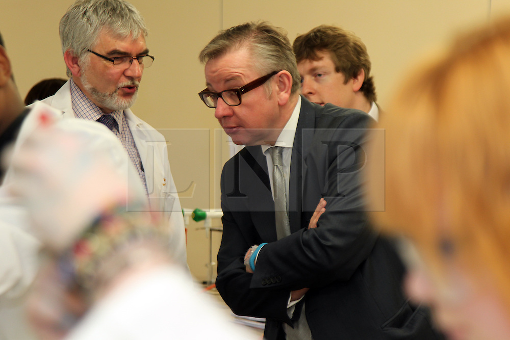 ©Licensed to London News Pictures. 04/04/2014<br /> Brooke Weston Academy, Corby, Northamptonshire. Secretary of State for Education Michael Gove MP visiting Brooke Weston Academy in Corby as part of a fact finding tour of free schools. Pictured, Michael Gove MP in Year 12 chemistry lesson with Head of Science Paul Knight.<br /> Photo credit: Steven Prouse/ LNP