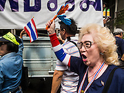 """20 DECEMBER 2013 - BANGKOK, THAILAND: A Thai woman marches down Silom Road during an anti-government protest in Bangkok. Thousands of anti-government protestors, supporters of the so called Peoples Democratic Reform Committee (PRDC), jammed the Silom area, the """"Wall Street"""" of Bangkok, Friday as a part of the ongoing protests against the caretaker government of Yingluck Shinawatra. Yingluck dissolved the Thai Parliament earlier this month and called for national elections on Feb. 2, 2014. The protestors want the elections postponed and the caretaker government to step down. The Thai election commission ruled Friday that the election would go on dispite the protests.          PHOTO BY JACK KURTZ"""