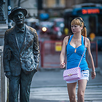 A woman walks past James Joyce's statue on the literary trail on the Gran Canale in Trieste, Italy