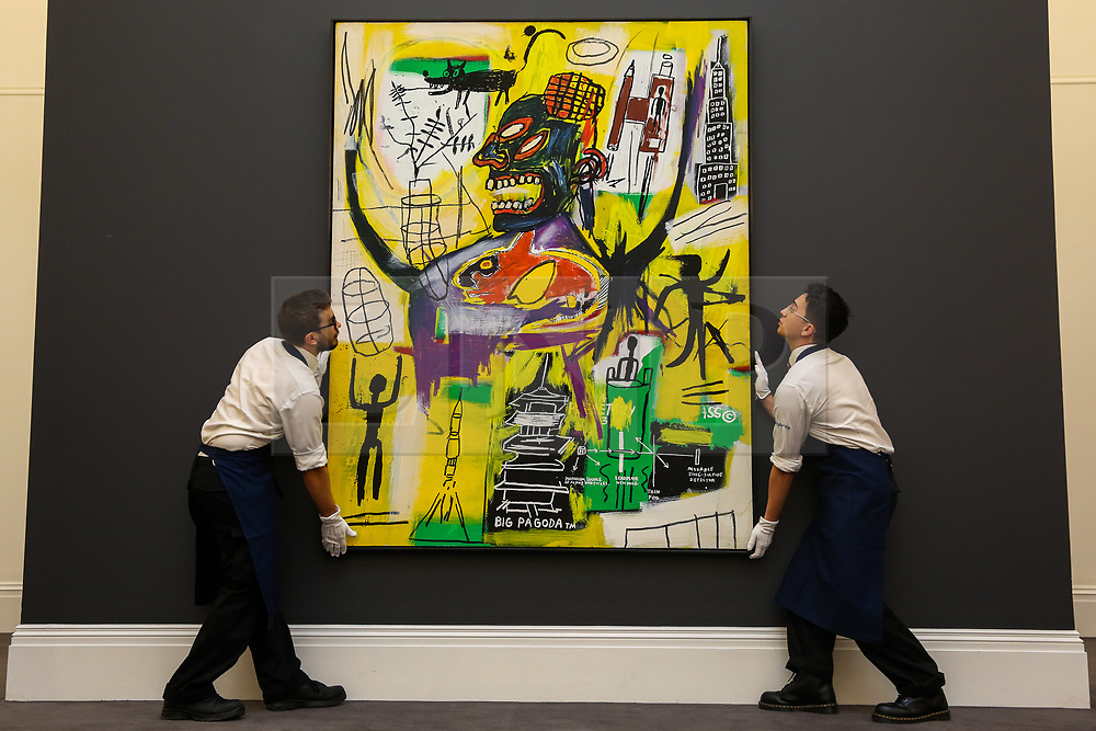 "© Licensed to London News Pictures. 27/09/2019. London, UK. Technicians hold Jean-Michel Basquiat's artwork titled ""Pyro"" during the preview of Sotheby's Frieze Week Contemporary Art Sale. The auction will take place on 3rd October 2019.  Photo credit: Dinendra Haria/LNP"