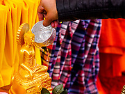 "29 APRIL 2017 - MINNEAPOLIS, MINNESOTA: A woman bathes a statue of the Buddha at Songkran Uptown. Several thousand people attended Songkran Uptown on Hennepin Ave in Minneapolis for the city's first celebration of Songkran, the traditional Thai New Year. Events included a Thai parade, a performance of the Ramakien (the Thai version of the Indian Ramayana), a ""Ladyboy"" (drag queen) show, and Thai street food.     PHOTO BY JACK KURTZ"