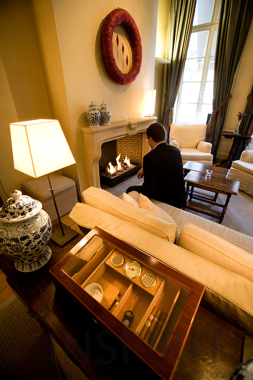 BRUSSELS - BELGIUM - 21 DECEMBER 2007 -- A man firing up the fireplace in Salon 3 in the lobby at Hotel Le Dixseptième seen from Rue de la Madeleine. On the table a bow with cigars.  Photo: Erik Luntang/