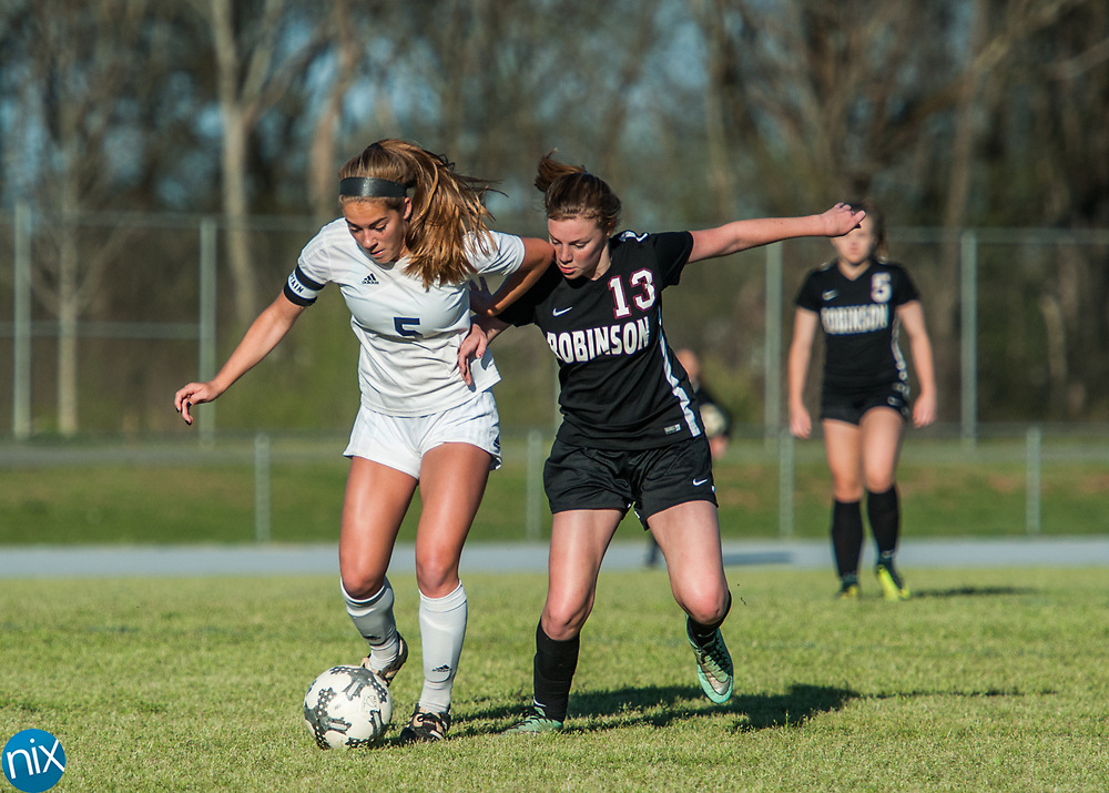 Hickory Ridge's Anna Keightley (5) and Jay M. Robinson's Marie Spokas (13) fight for the ball Friday night at Hickory Ridge High School in Harrisburg. The game ended in a 2-2 draw after double overtime.