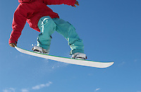 Teenage snowboarder jumping cropped