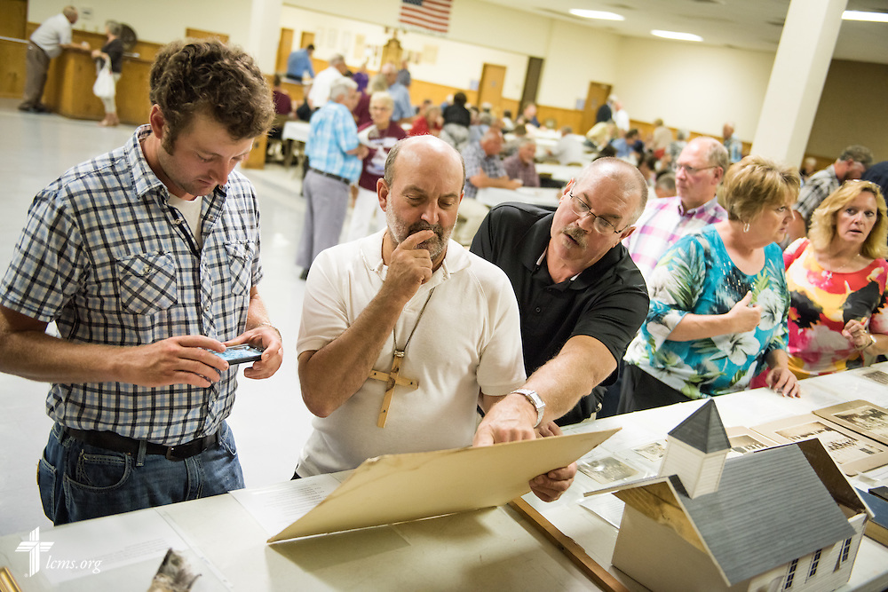 "(L-R) Randy Langrehr, Bob Langrehr, and Doug Brinkman survey church memorabilia from St. John's Lutheran Church in New Minden, Ill., during a fellowship meal at the Knights of Columbus hall in Carlyle, Ill., on Sunday, August 9, 2015. The fellowship meal was a part of activities during a ""Day of Thanksgiving and Rededication""  at St. John's Lutheran Church in New Minden, Ill.  LCMS Communications/Erik M. Lunsford"