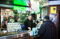 "NAPLES, ITALY - 12 DECEMBER 2014: Pino De Stasio, owner of cafè Bar Settebello, operates the cash register in his cafè in Naples, Italy, on December 12th 2014. Bar Settebello is part of the ""Rete del Caffè Sospeso"" (Suspended Coffee Network).<br /> <br /> A caffè sospeso,or suspended coffee, is a cup of coffee paid for in advance as an anonymous act of charity. The tradition began in the working-class cafés of Naples, where someone would order a sospeso, paying the price of two coffees but receiving and consuming only one. A poor person enquiring later whether there was a sospeso available would then be served a coffee for free."